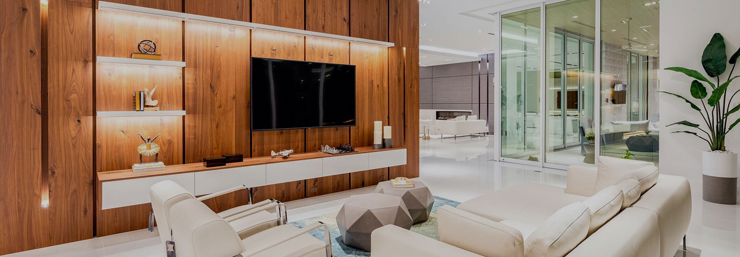 a stately living room with wood entertainment wall and hurricane rated patio sliding glass doors